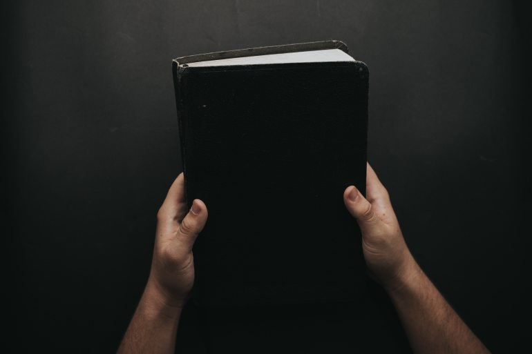 person-holding-black-cover-bible-2258240